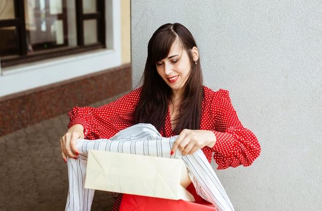スマイリーの女性は彼女のセールのショッピングアイテムに興奮しています