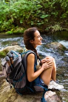バックパックで自然を探索するスマイリー女性
