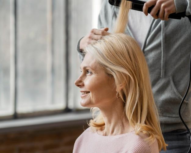 Donna sorridente che ottiene i suoi capelli raddrizzati dal parrucchiere a casa