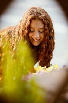 春の花を屋外で取得するスマイリー女性