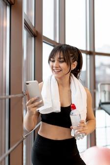 Donna di smiley in palestra in pausa utilizzando mobile
