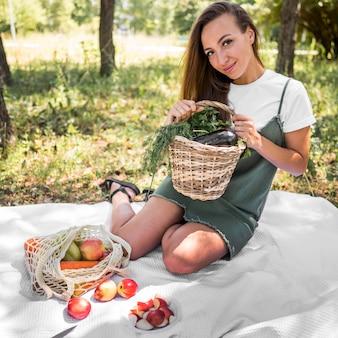 健康的なスナックとピクニックを持つスマイリー女性