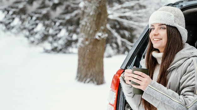 Смайлик женщина с теплым напитком во время поездки с копией пространства