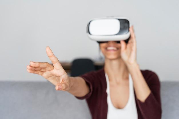 Donna sorridente che si diverte a casa con le cuffie da realtà virtuale