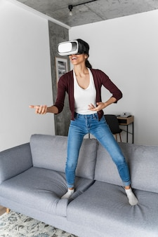 Smiley woman having fun at home with virtual reality headset