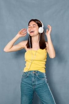 ヘッドフォンを着て楽しんでいるスマイリー女性