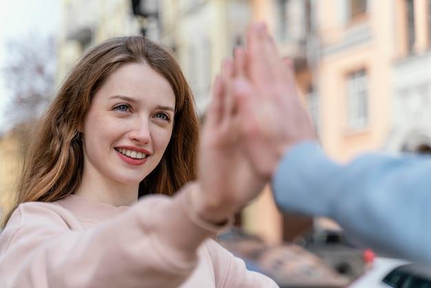 Donna sorridente che si diverte con gli amici in città