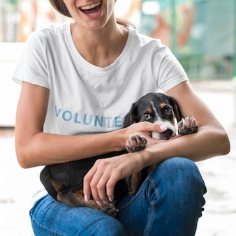 Smiley woman holding adorable rescue dog at shelter