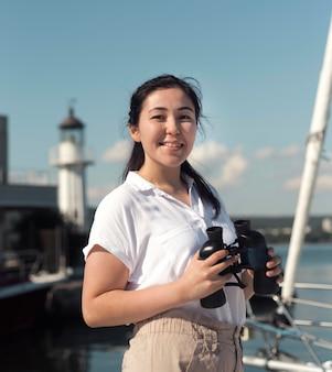 Smiley woman holding binoculars