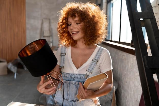 Смайлик женщина, держащая книгу и лампу для украшения нового дома
