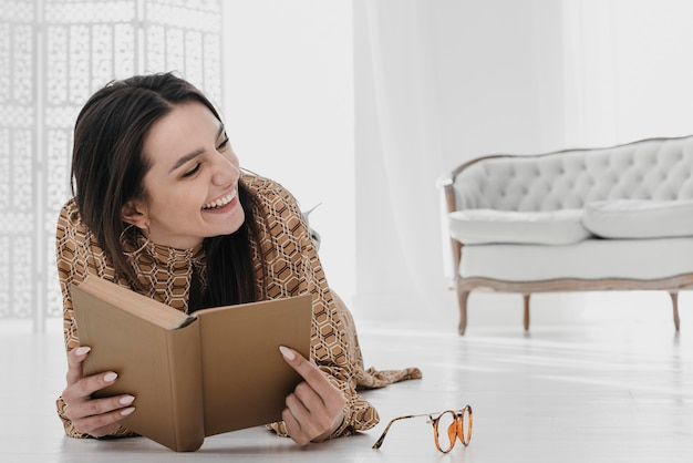 Smiley woman holding book at home