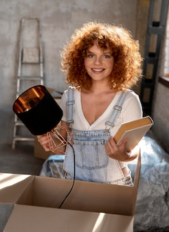 Smiley woman holding book and lamp for decorating new home
