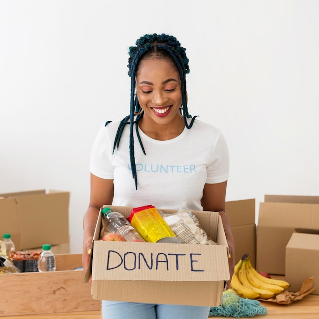 Smiley woman holding a box of donations