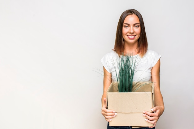 Smiley woman holding a box with copyspace