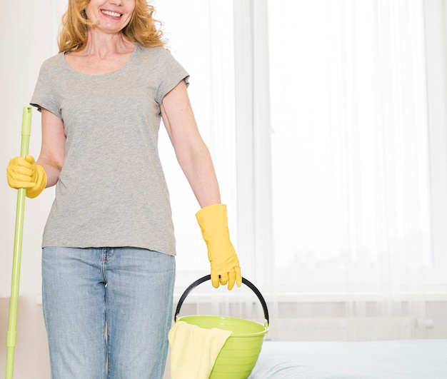 Smiley woman holding bucket and mop