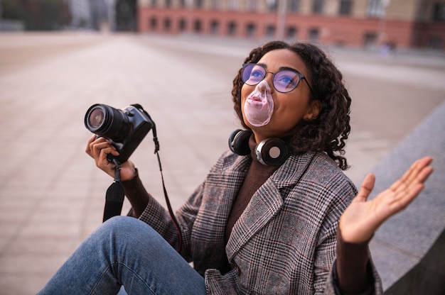 Smiley woman holding camera and blowing bubbles