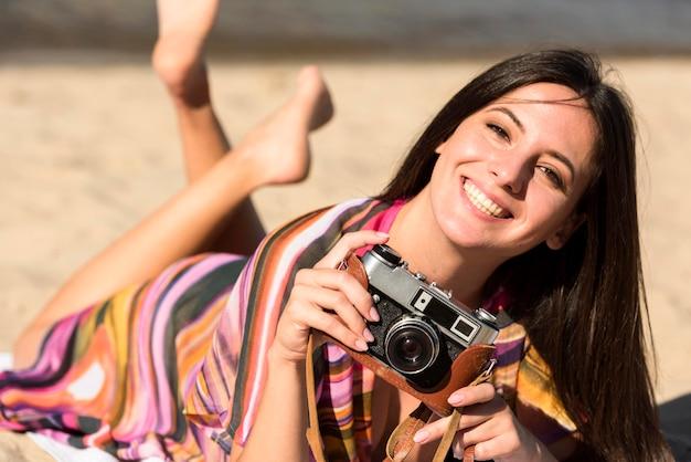 ビーチの砂の上に座っている間カメラを保持しているスマイリー女性