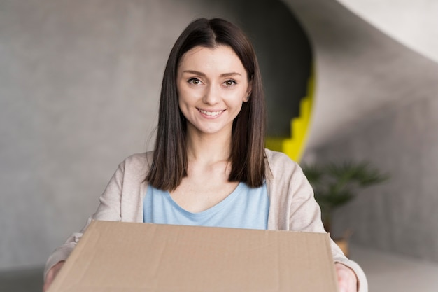 段ボール箱を抱えて笑顔の女性