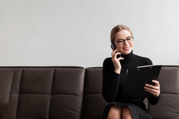 Smiley woman holding clipboard and talking over phone