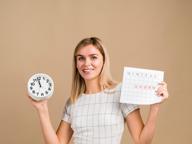 Smiley woman holding a clock and her period calendar