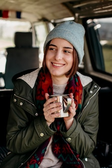 Smiley woman holding a coffee cup in a van