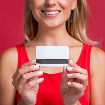 Смайлик женщина, держащая кредитную карту