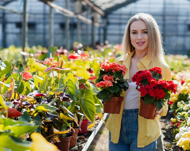 Smiley woman holding flower pots