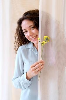 Donna sorridente con fiori in mano, colpo medio
