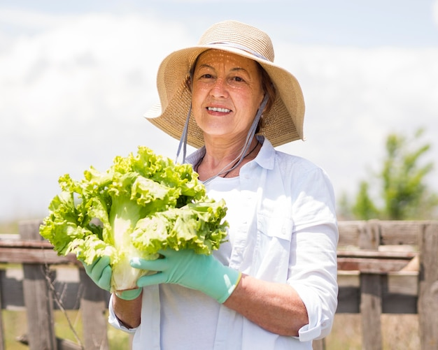 Smiley woman holding a fresh cabbage