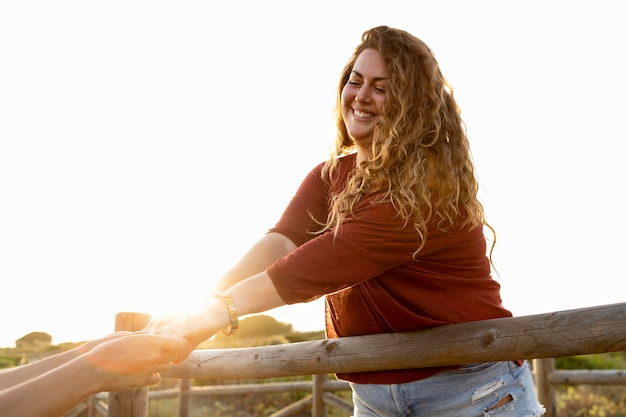 Smiley woman holding friend's hand outdoors