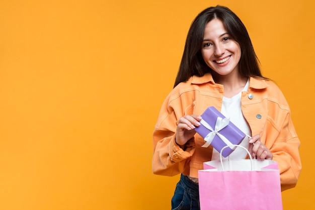 Смайлик женщина, держащая подарок и хозяйственную сумку с копией пространства