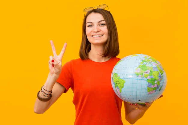 Smiley woman holding globe and making peace sign