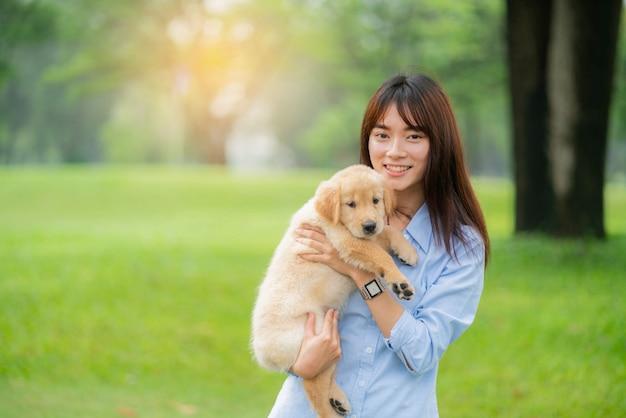 庭でゴールデン・リトリーバーの子犬を保持しているスマイリー女性