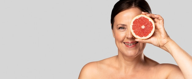 Smiley woman holding half of grapefruit over face with copy space