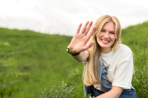 Smiley woman holding hand up while posing in nature