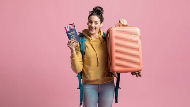 Smiley woman holding health passport and luggage