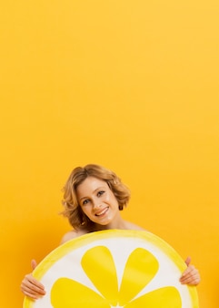 Smiley woman holding lemon slice