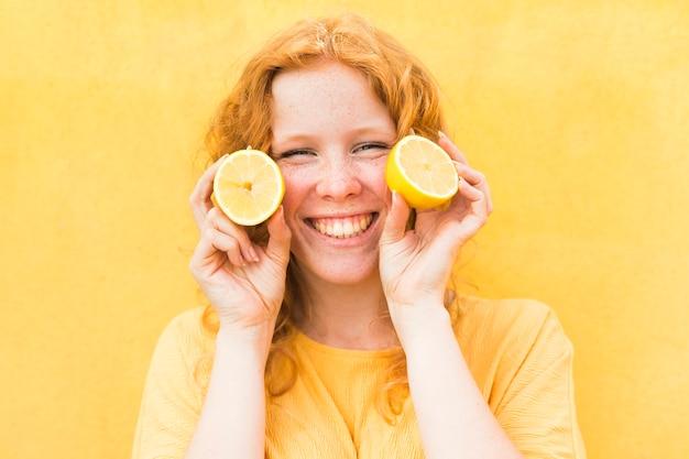 レモンを保持しているスマイリー女性