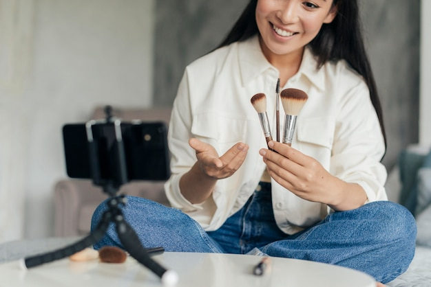 Smiley woman holding make up brushes while vlogging