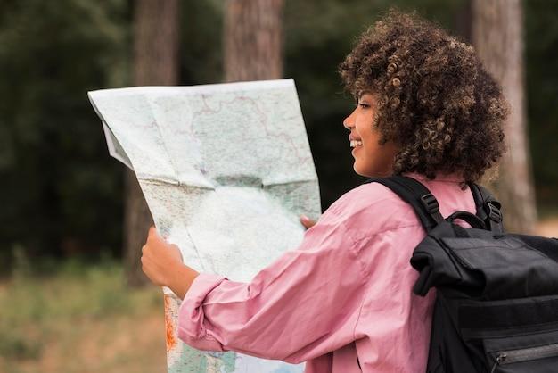Donna di smiley che tiene mappa mentre si accampa all'aperto
