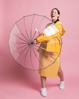 Smiley woman holding an opened umbrella