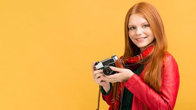 写真のカメラを保持しているスマイリー女性