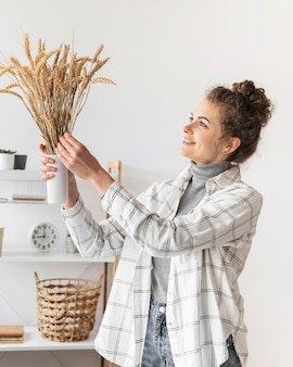 Smiley woman holding plants medium shot