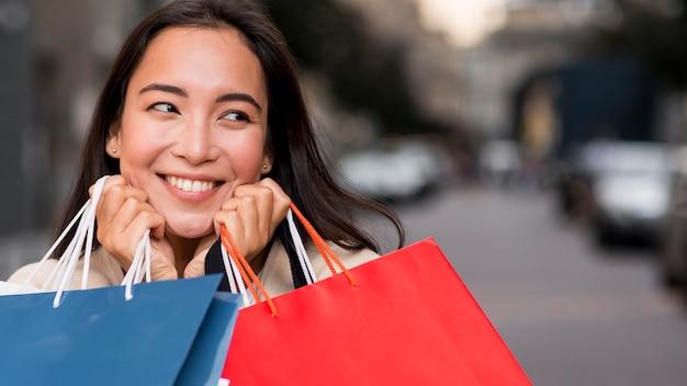 販売ショッピング後の買い物袋を保持しているスマイリー女性