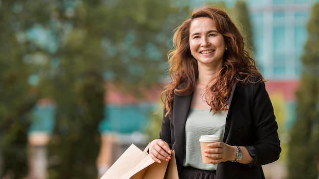Smiley woman holding shopping bags and a cup of coffee