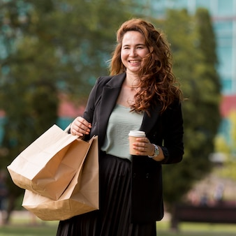 Donna sorridente che tiene i sacchetti della spesa all'esterno