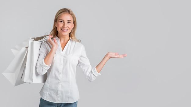 Donna sorridente che tiene le borse della spesa e mostra lo spazio alla sua sinistra