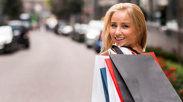 Donna di smiley che tiene i sacchetti della spesa mentre posa all'aperto