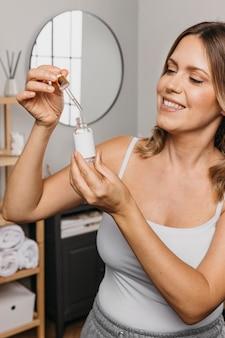 Donna sorridente che tiene un prodotto per la cura della pelle senza etichetta