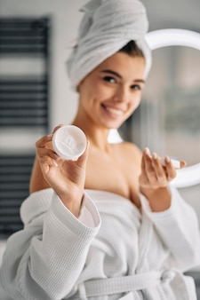 Smiley woman holding a skincare cream